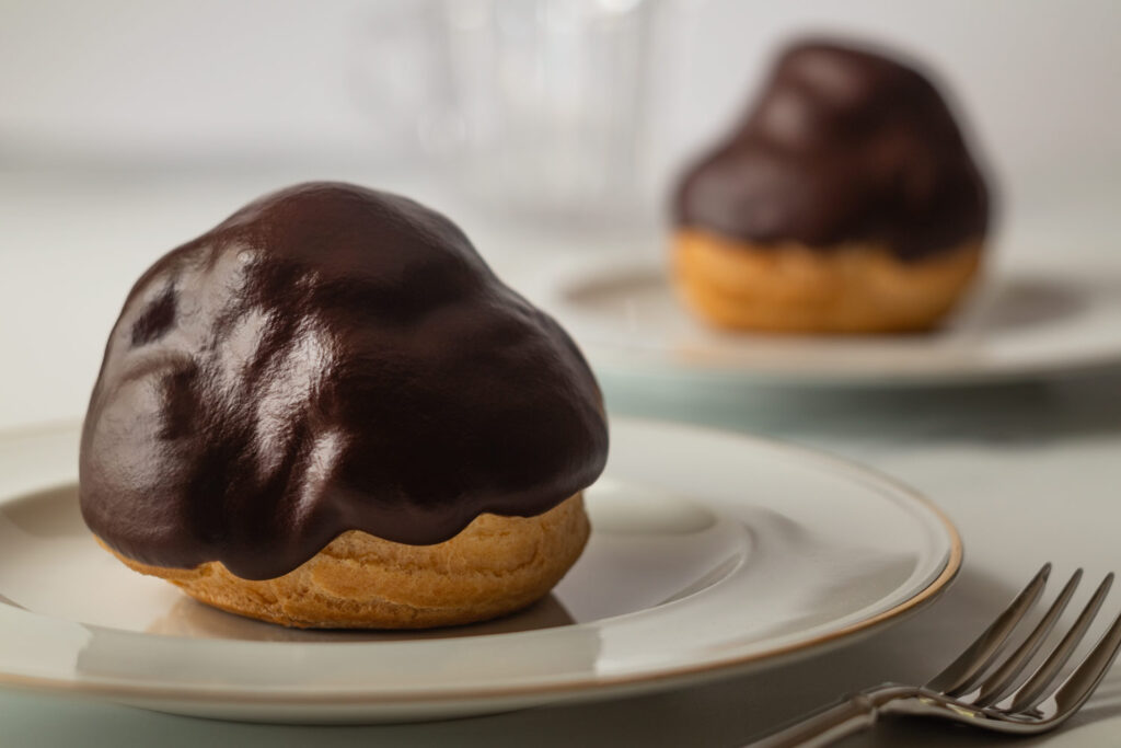 two Dutch profiteroles on fancy place settings