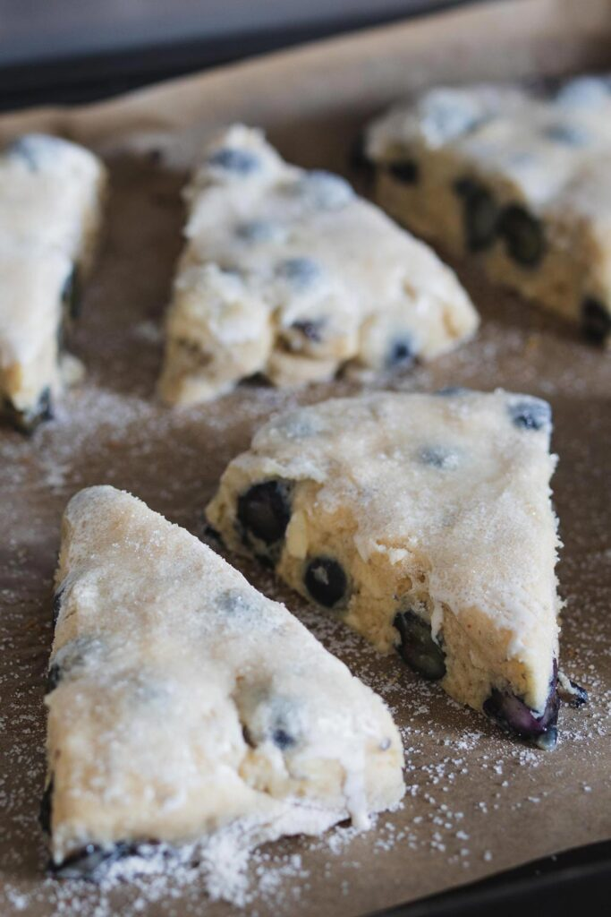 Brush scones with cream and sprinkle with sugar