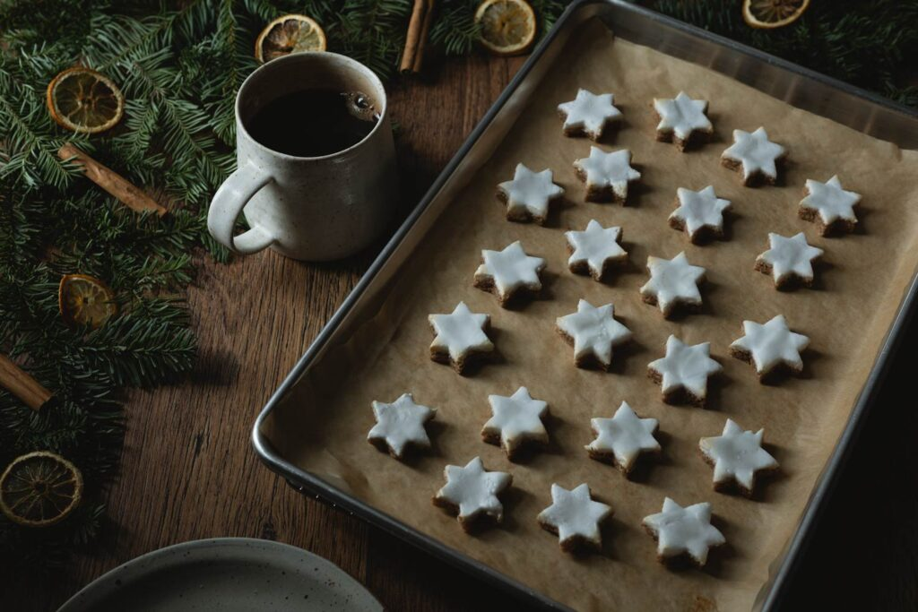 baking tray of zimtsterne cinnamon star cookies with garland and a mug of coffee