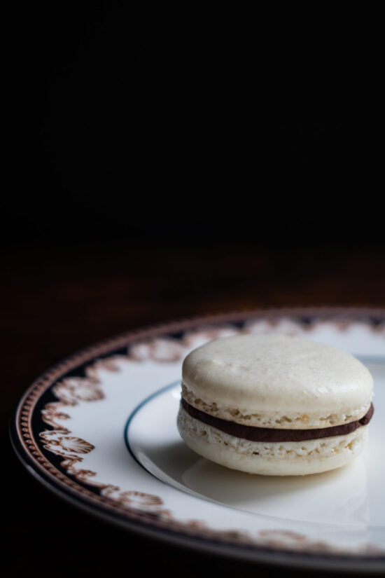 almond macaron with dark chocolate ganache on porcelain plate