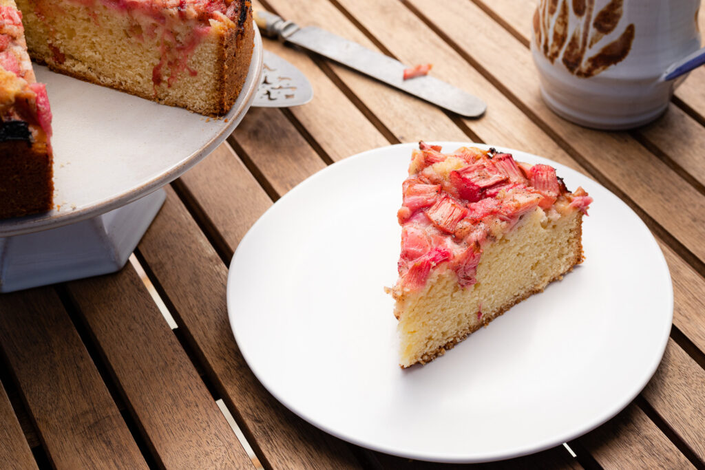 a slice of rhubarb cake on a white plate with a coffee mug, knife, and cake stand