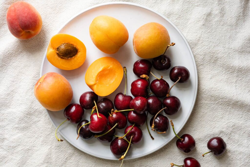 sweet cherries and fresh apricots on a white plate