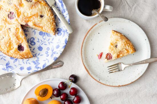 bublanina cake on a blue floral plate, silver-plated cake server, a plate of cherries and apricots, a cup of coffee, and a slice of cake