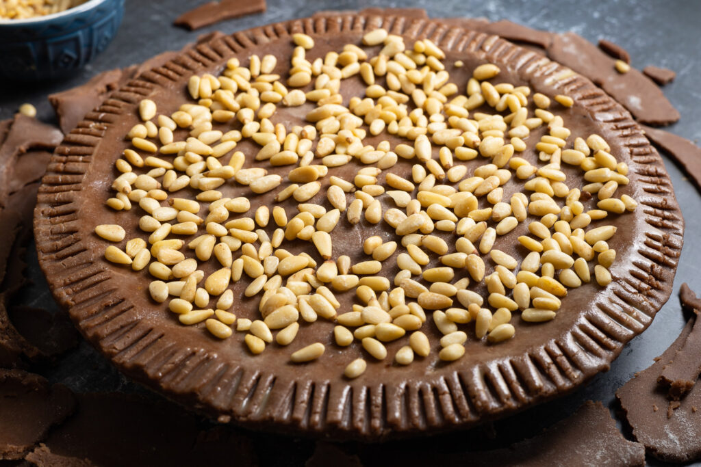 pine nuts scattered on the top of the chocolate torta della nonna