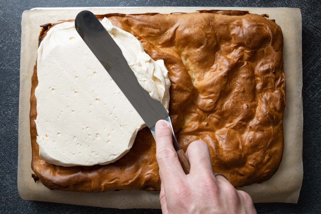 spreading the krem filling onto the pastry with an offset spatula